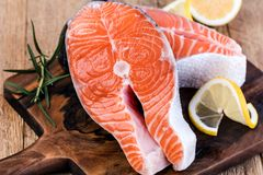 Slice of red fish salmon. With lemon; rosemary on a wooden table Stock Photo
