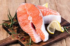 Slice of red fish salmon. With lemon; rosemary on a wooden table Royalty Free Stock Images