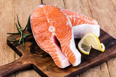 Slice of red fish salmon. With lemon; rosemary on a wooden table Stock Photos