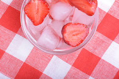 A slice of red strawberry on glass plate in party theme background Stock Photography