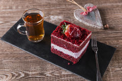Slice of red velvet cake with white frosting is garnished with strawberries  close up Royalty Free Stock Image