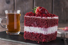 Slice of red velvet cake with white frosting is garnished with strawberries close up Stock Image