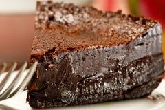 Slice of rich dark chocolate cake. A slice of rich dark moist chocolate cake with a fork in the front Royalty Free Stock Photo