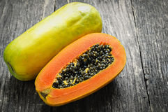 Slice of ripe papayas on wooden table Stock Images