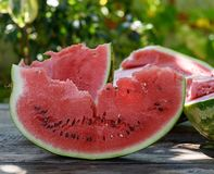 Slice of ripe red watermelon with seeds. On a wooden table, close up stock photo