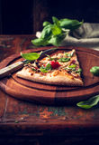 Slice of rustic pizza topped with fresh basil Stock Images