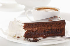 Slice of Sacher cake in plate with coffee Stock Images