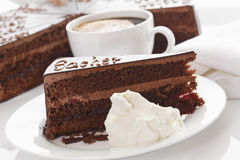 Slice of Sacher cake in plate with coffee Stock Photo