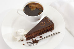 Slice of Sacher cake in plate with coffee Royalty Free Stock Photography
