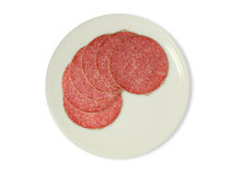 Slice of salami. Six slices of salami on a white plate Stock Photo