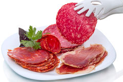 Slice of salami and meat products on white plate Royalty Free Stock Photos