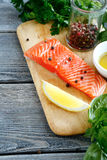 Slice of Salmon with basil and olive oil on board Stock Image