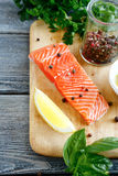 Slice of Salmon with basil and pepper on the board Stock Photography