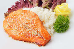 Slice of salmon with garnish. Syake teriyaki - peace of roasted salmon with rice, parsley, lemon and sesame on a white background Stock Photo
