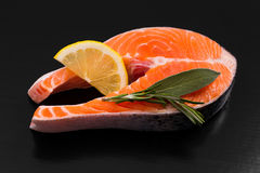 Slice of salmon steak with lemon and herbs Stock Photos