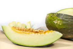 Slice of Santa Claus melon with seeds, on white Royalty Free Stock Image