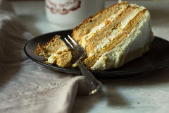 Slice of simple homemade carrot and honey cake with cream cheese frosting on a dark plate, broken off piece with fork, cup of coff Royalty Free Stock Photos