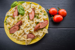 Slice sliced grilled sausage with pasta, slices of bread, herbs and cherry tomatoes. top view. wooden black background..  . Close- Royalty Free Stock Photo
