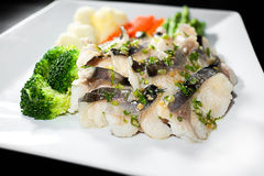 Slice steamed fish with braised leeks topping and spicy sauce in Stock Photos