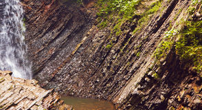 Slice of stone rocks geological background with a waterfall Stock Photo