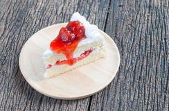 Slice of strawberry cake on wood plate Stock Images