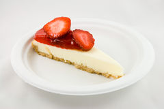 Slice of Strawberry Cheesecake. Slice of strawberry chessecake on a white plate with a white background Stock Photography