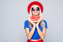 Slice of summer goodness. Beautiful young woman holding slice of watermelon and smiling while standing isolated on gray Stock Photography