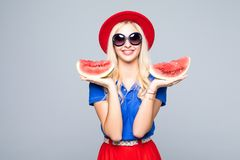 Slice of summer goodness. Beautiful young woman holding slice of watermelon and smiling while standing isolated on gray Stock Photo