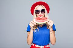 Slice of summer goodness. Beautiful young woman holding slice of watermelon and smiling while standing isolated on gray Stock Images
