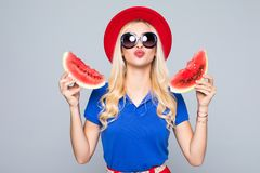 Slice of summer goodness. Beautiful young woman holding slice of watermelon and smiling while standing isolated on gray Royalty Free Stock Photos