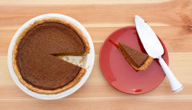 Slice taken from a pumpkin pie with pie server Royalty Free Stock Images
