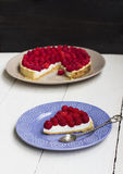 Slice of a tart with raspberry on a plate. Slice of a tart with raspberry on a violet plate Royalty Free Stock Image