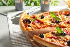 Slice of tasty pizza on shovel, closeup. Slice of tasty pizza with cheese, olives and sausages on shovel, closeup stock photos