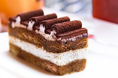 A Slice of Tiramisu Cake. With Cream and Chocolate Roll Icing at Cafe on Summer. Italian Dessert Concept stock photo