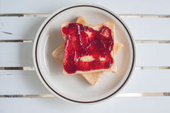 Slice of toast bread with jam. Closeup top view of slice of toast bread with jam on wood table Royalty Free Stock Photo