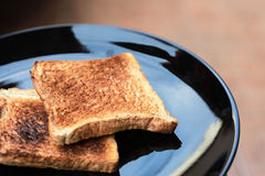 Slice toasted bread on black dish. Royalty Free Stock Photography