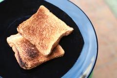 Slice toasted bread on black dish. Stock Photo
