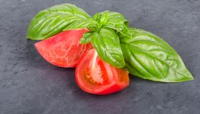 Slice of tomato with basil leaves. On black stone royalty free stock photography