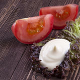 Slice of tomato. handful of mayonnaise swirl on green leaf royalty free stock images