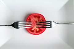 Slice of tomato on a white plate and two forks Royalty Free Stock Image