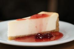 Slice of traditional new york cheesecake with strawberry jam on white plate on wood table. Shallow focus Stock Image