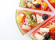 Slice of tropical fruit watermelon pizza. Close up overhead detail of a slice of tropical fruit watermelon pizza topped with kiwifruit, blueberries, orange stock photography
