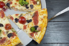 Slice of vegetarian pizza on dark table Royalty Free Stock Image