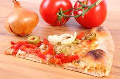 Slice of vegetarian pizza, tomatoes and onion on wooden surface Royalty Free Stock Photo