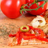Slice of vegetarian pizza, tomatoes and seasoning on wooden surface Royalty Free Stock Image