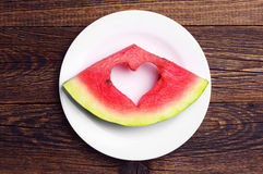 Slice of watermelon. With cut in the heart shape on white plate. Top view stock photos