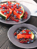 Slice of watermelon pizza cake with berries. Slice of watermelon served as cake or pizza with fresh berries on rustic background royalty free stock images