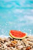 Slice of watermelon at seashore Stock Image