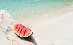 Slice of watermelon on timber against beach background. Royalty Free Stock Images