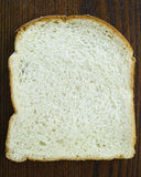 Slice of White Bread. A single slice of white bread on a wood table Royalty Free Stock Image